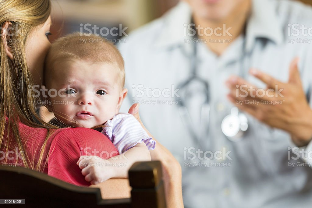 Mother holding baby with cystic fibrosis during pediatric appointment stock photo