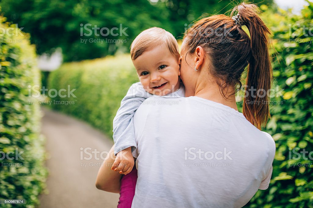 Mother holding child in park stock photo