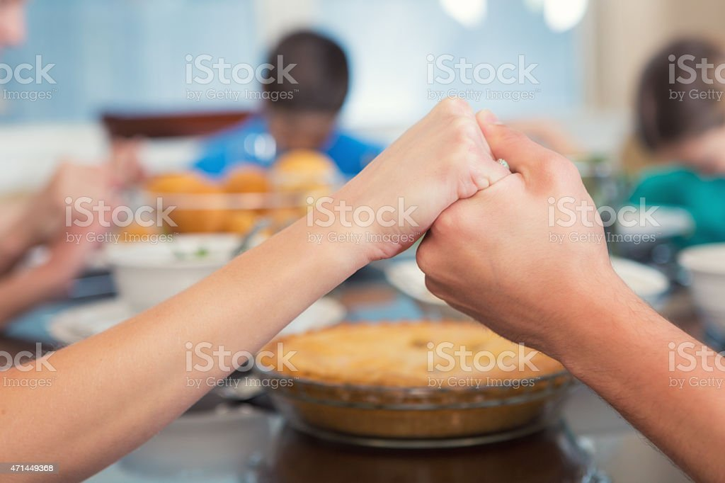 Mother holding daughter's hand while they pray over meal stock photo