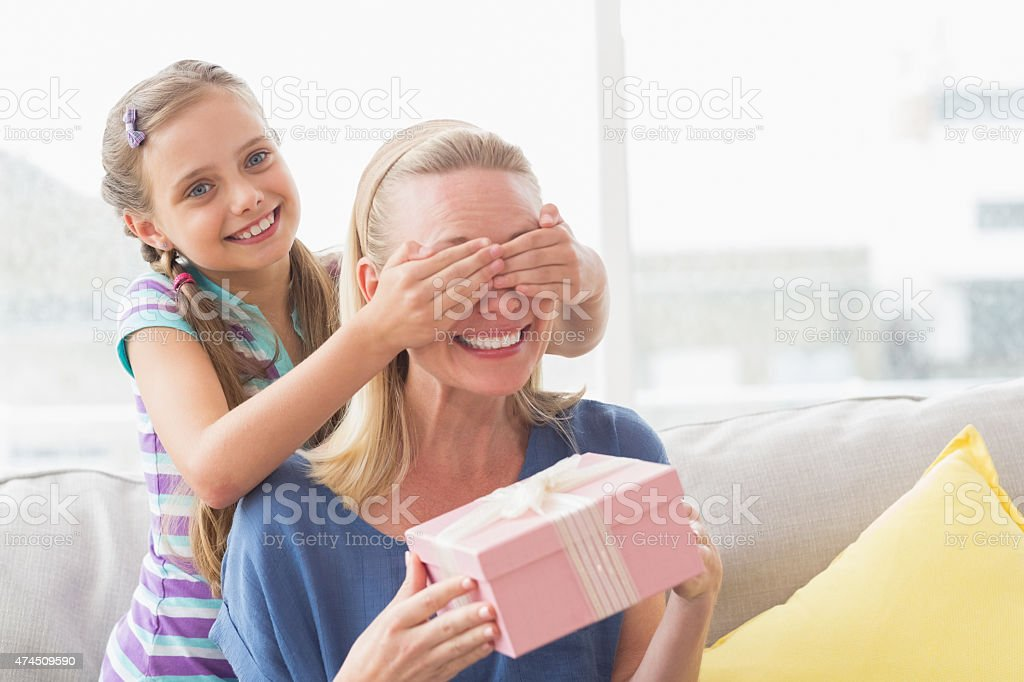Mother holding gift with daughter covering her eyes stock photo