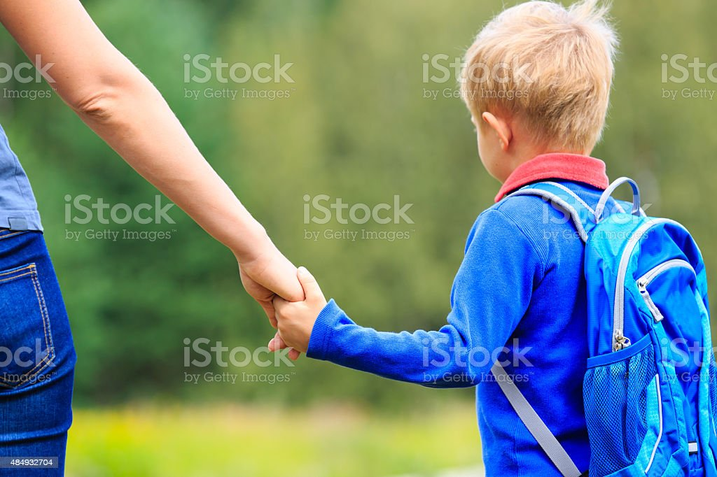 Mother holding hand of little son with backpack outdoors stock photo