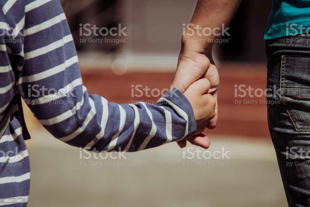 Mother holding hand of little son with backpack stock photo