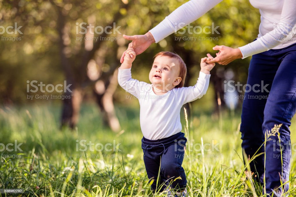 Mother holding hands of her son making first steps stock photo