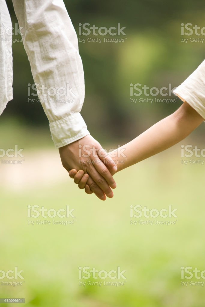 Mother holding hands with children stock photo