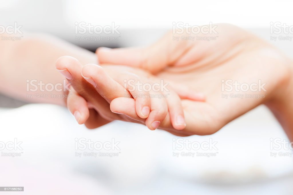 Mother holding her babies hand stock photo