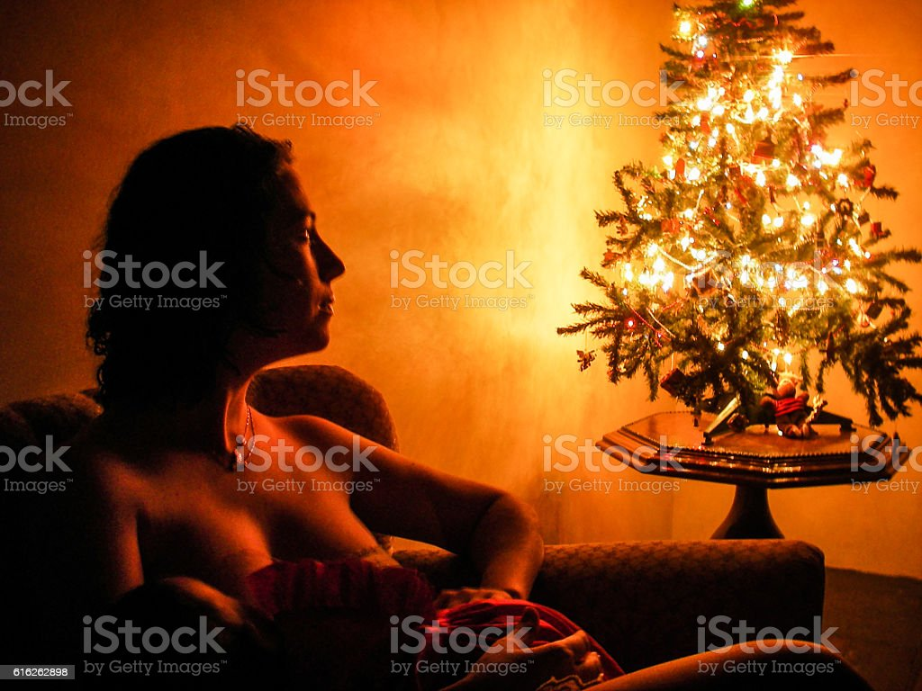 Mother Holding Her Baby Lit by Chritsmas Tree stock photo