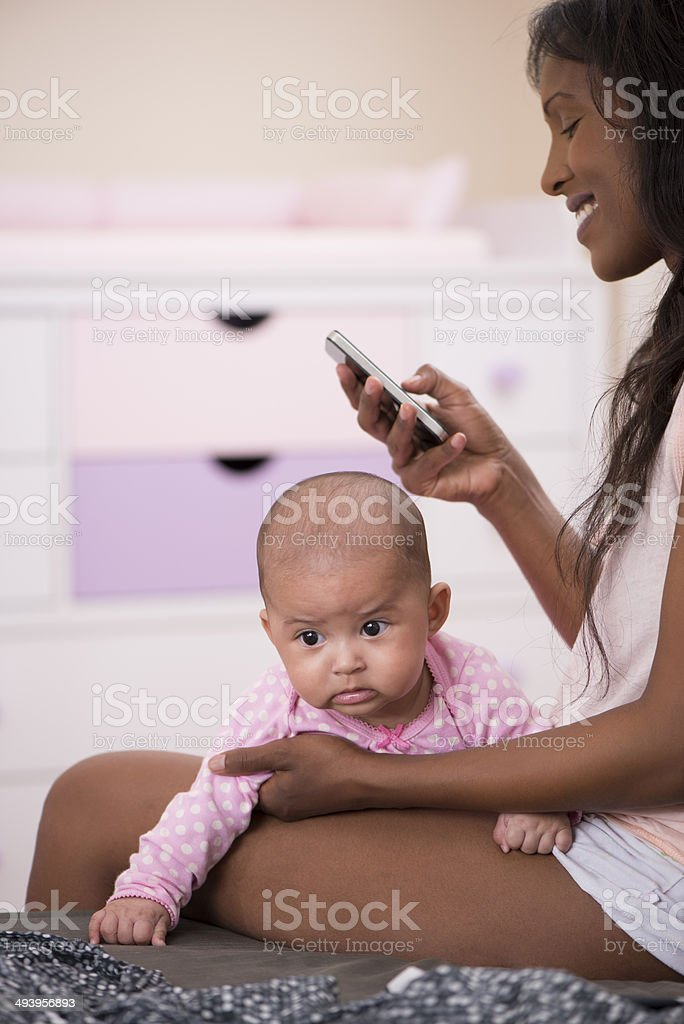 Mother holding her baby  while using phone. stock photo