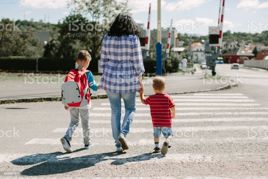 Mother holding her children and crossing a road on way to school stock photo