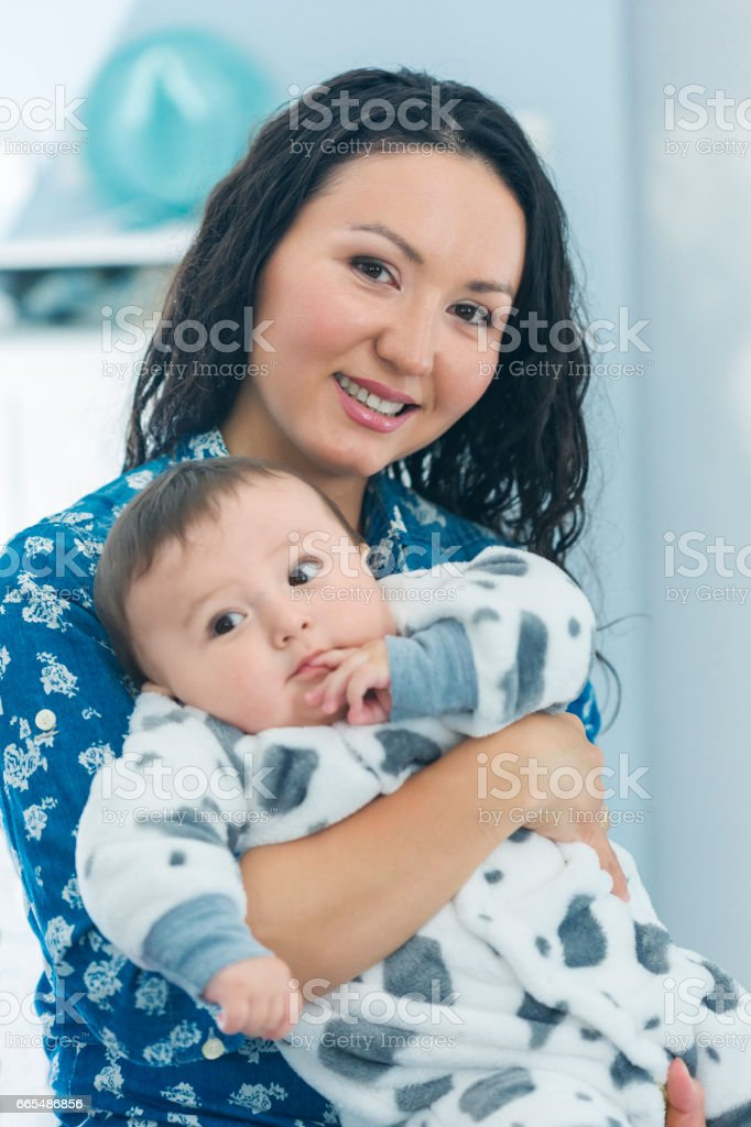 Mother holding her little son in her arms smiling happily stock photo