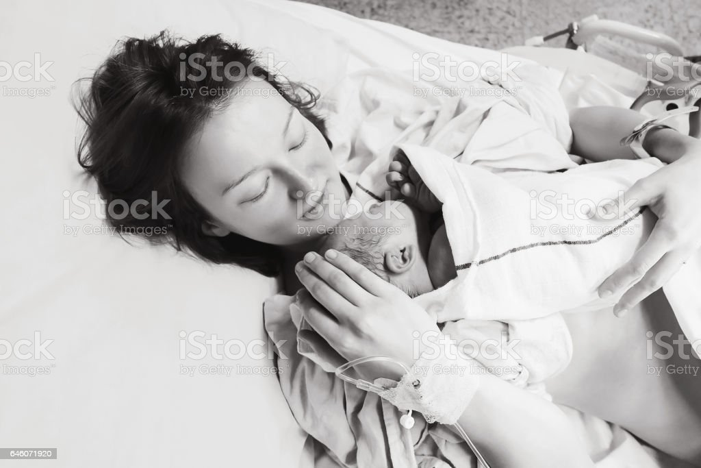 Mother holding her newborn baby child after labor in a hospital. stock photo