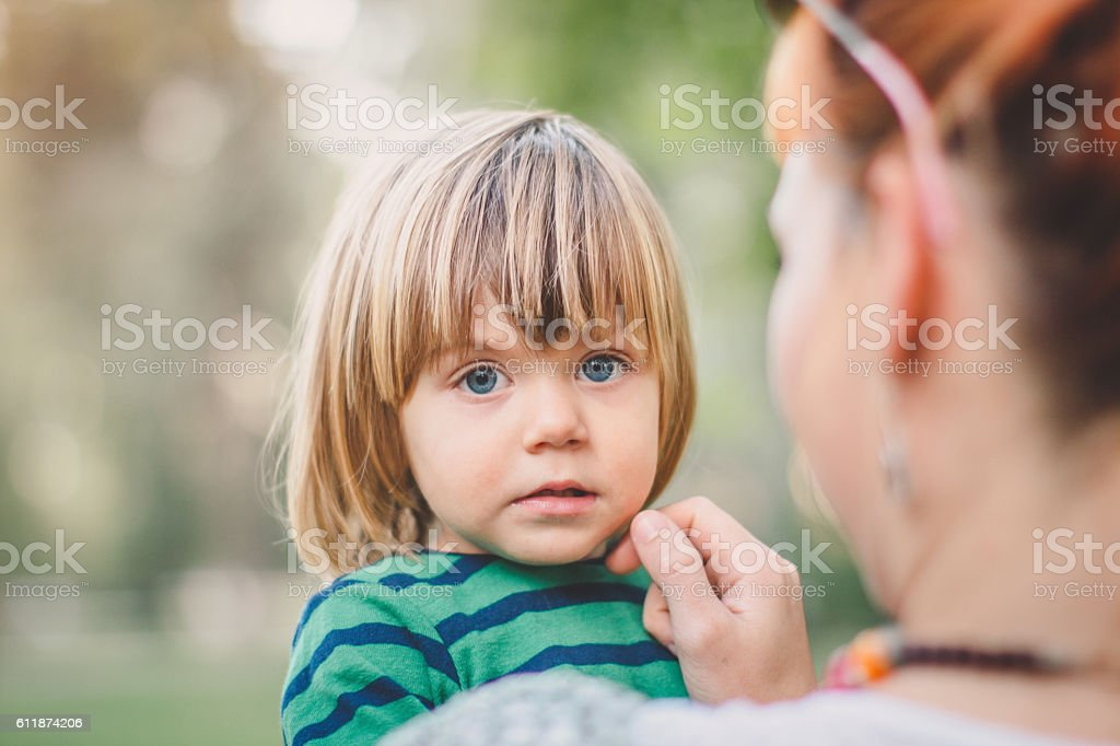 Mother holding her son in green park. Love concept stock photo