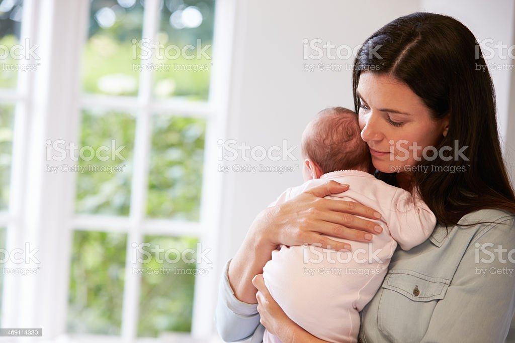 Mother holding new born baby on her chest stock photo