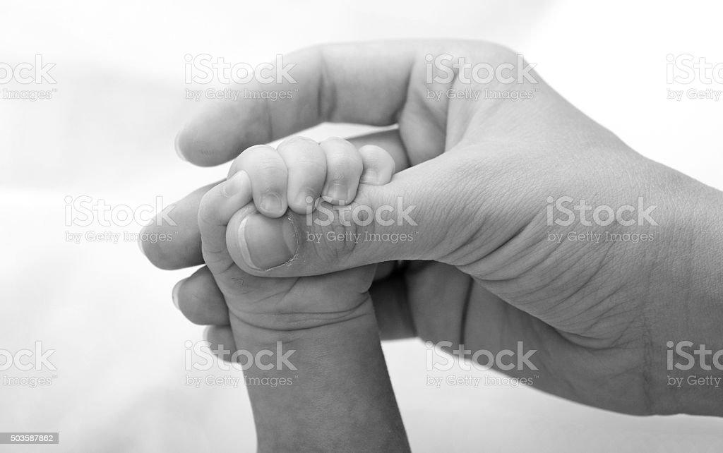 Mother holding newborn baby hand stock photo