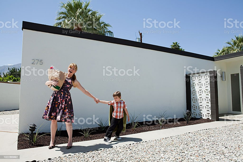 Mother holding shopping bag and pulling son's arm stock photo
