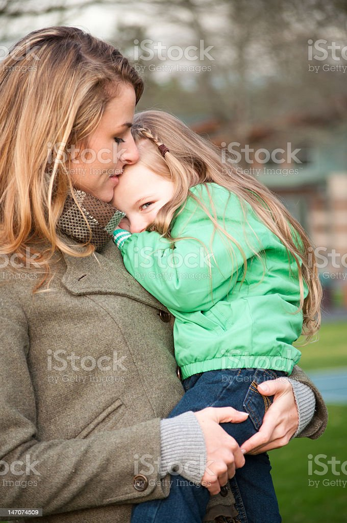 Mother holding shy smiling girl royalty-free stock photo