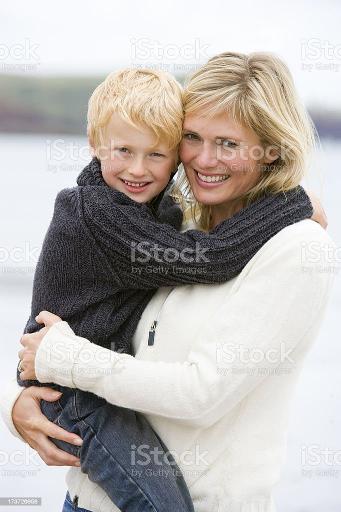 Mother holding son at beach smiling royalty-free stock photo