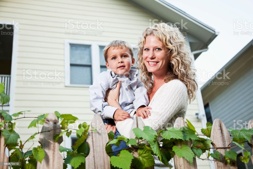 Mother holding son in back yard stock photo