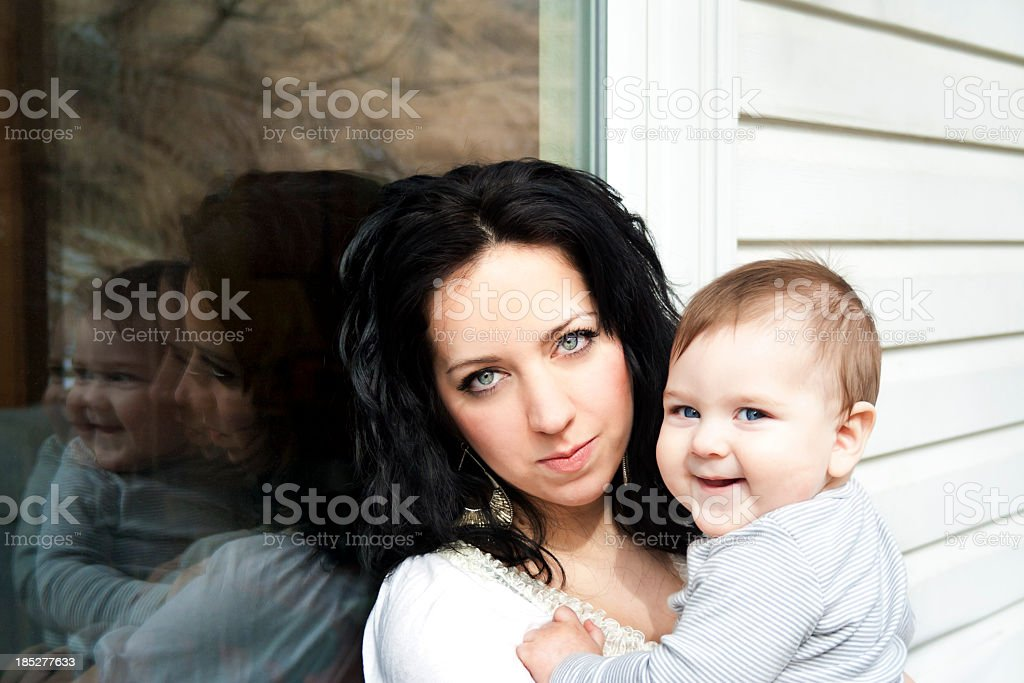 Mother holds baby while leaning against window stock photo