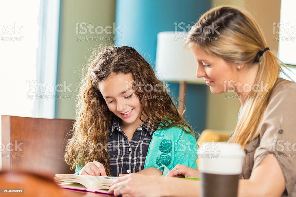 Mother homeschool elementary age daughter in public library stock photo