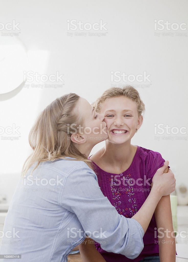 Mother hugging and kissing smiling daughter royalty-free stock photo