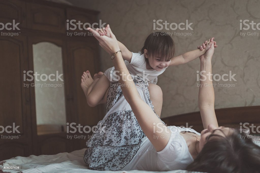 Mother hugging and playing with his daughter in bed, lifestyle, stock photo