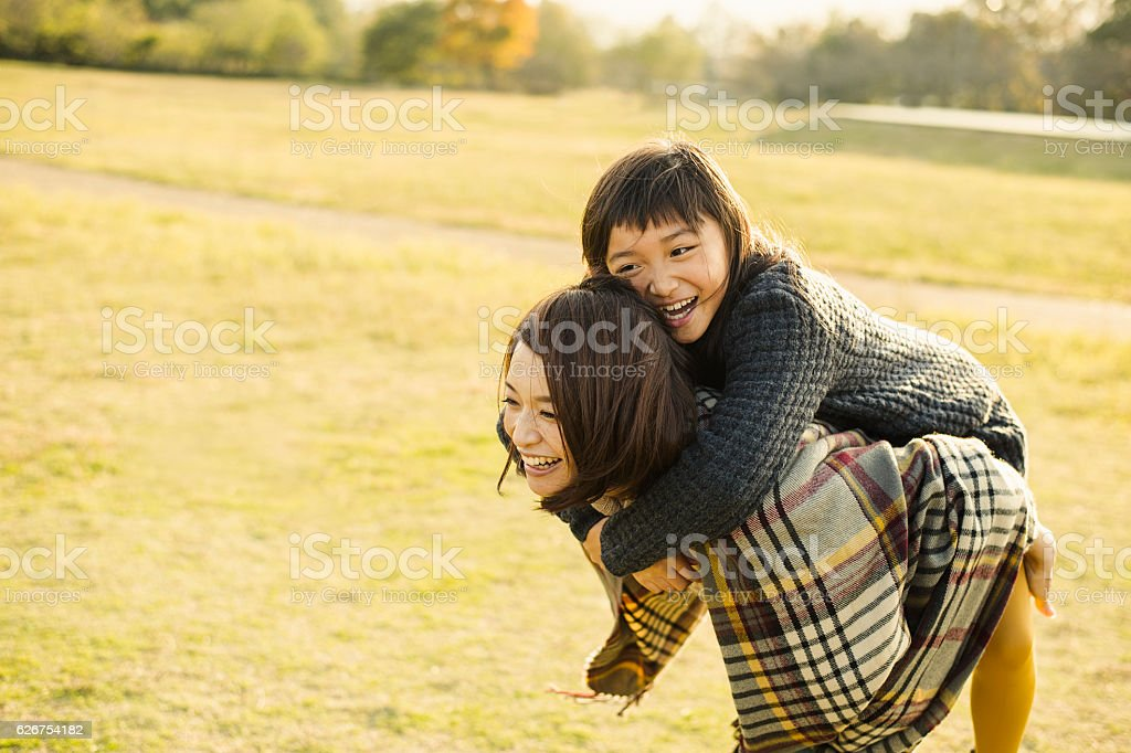 Mother hugging daughter in outdoors stock photo