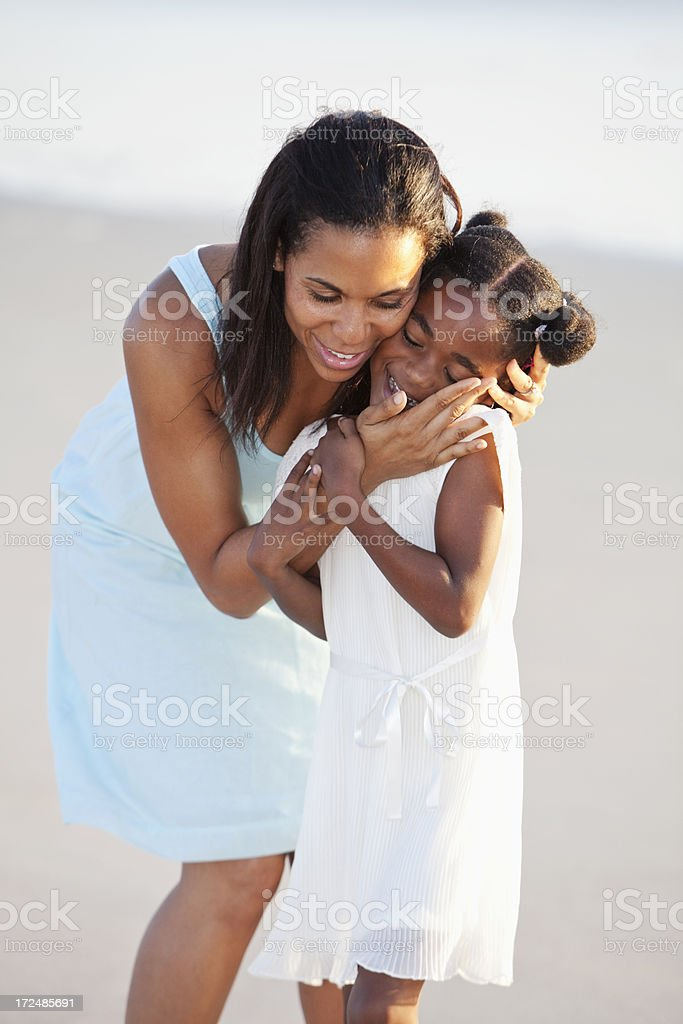 Mother hugging daughter stock photo
