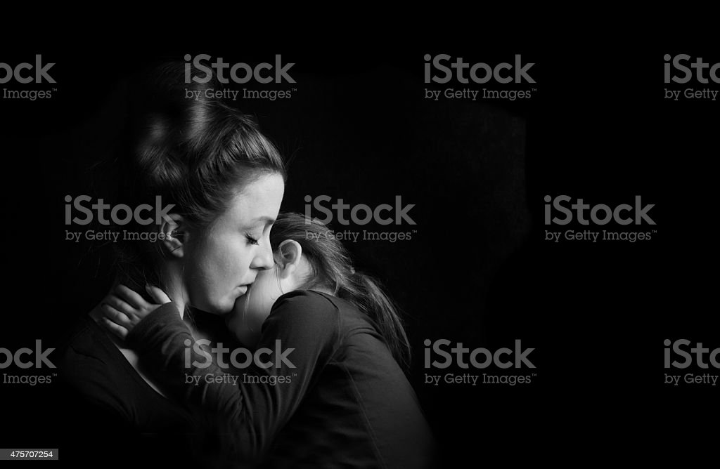 Mother Hugging Daughter Tenderly stock photo