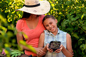 Mother hugging her daughter holding a plant before planting
