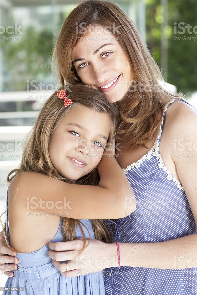 Mother hugging her daughter stock photo
