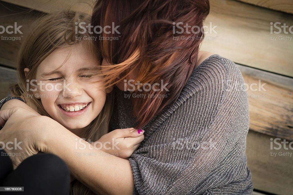 Mother Hugging Little Daughter While Sitting Outdoors royalty-free stock photo