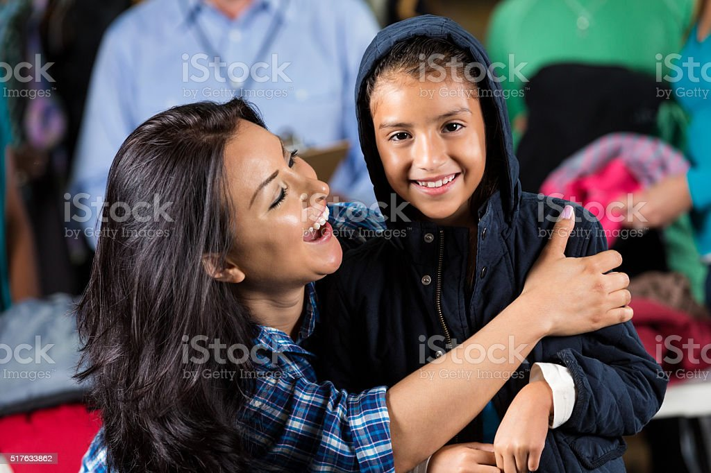 Mother hugs daughter at clothing drive stock photo