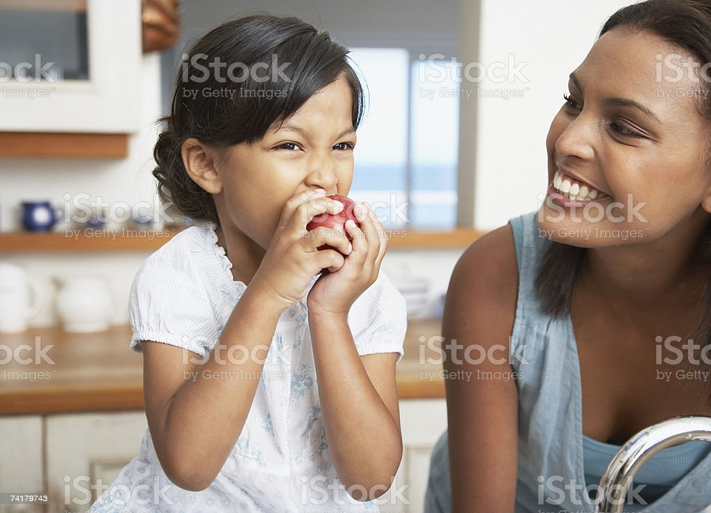 Mother in kitchen with daughter eating red apple royalty-free stock photo