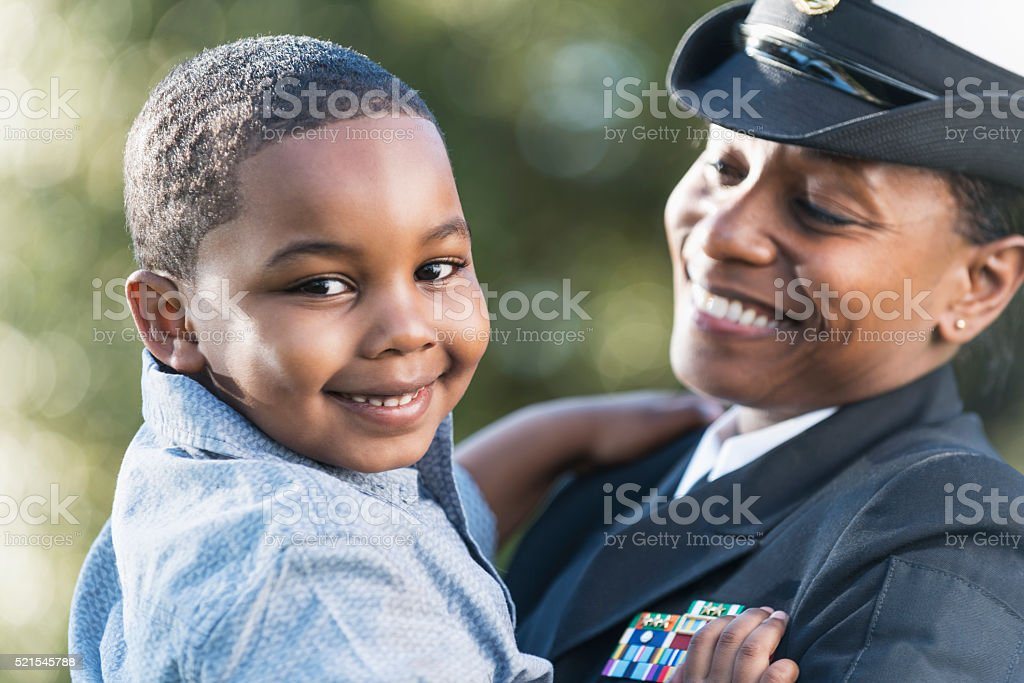 Mother in navy officer uniform holding son stock photo
