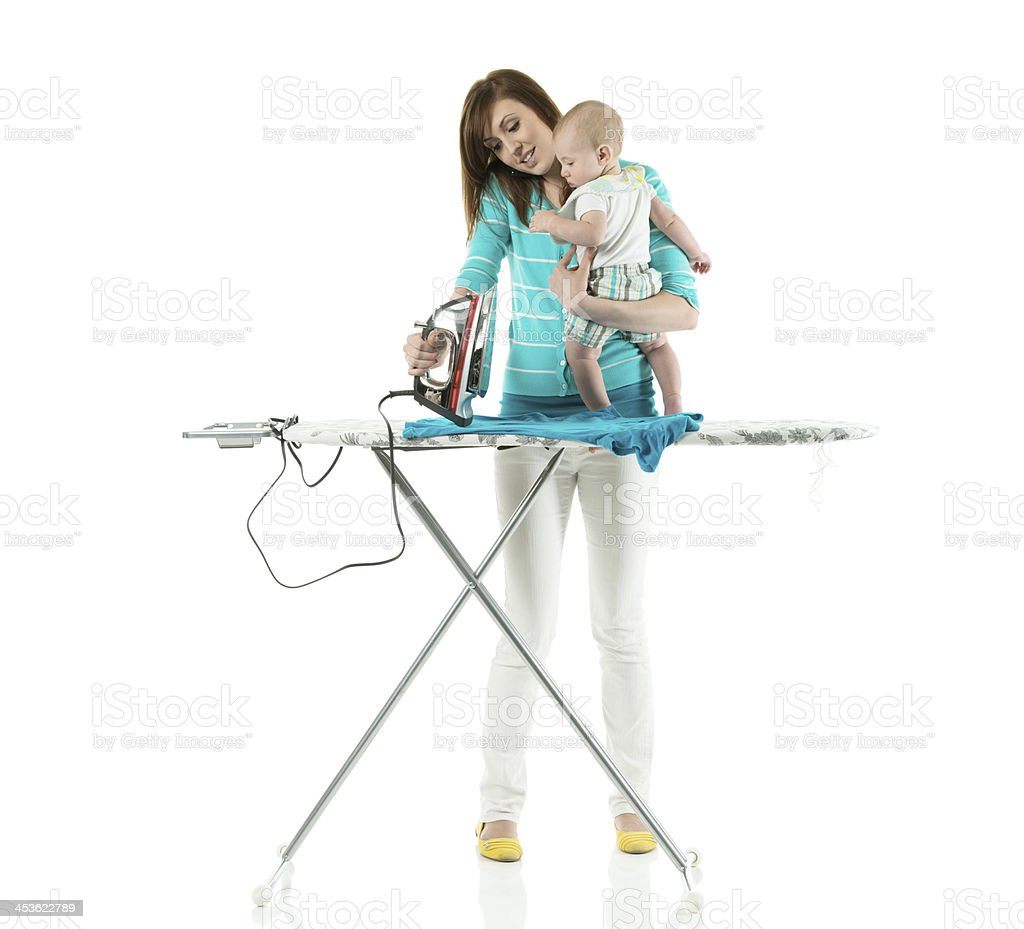 Mother ironing clothes while carrying her baby stock photo