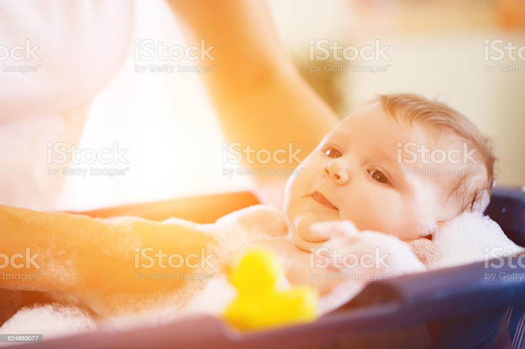 Mother is bathing her baby in bathtub stock photo