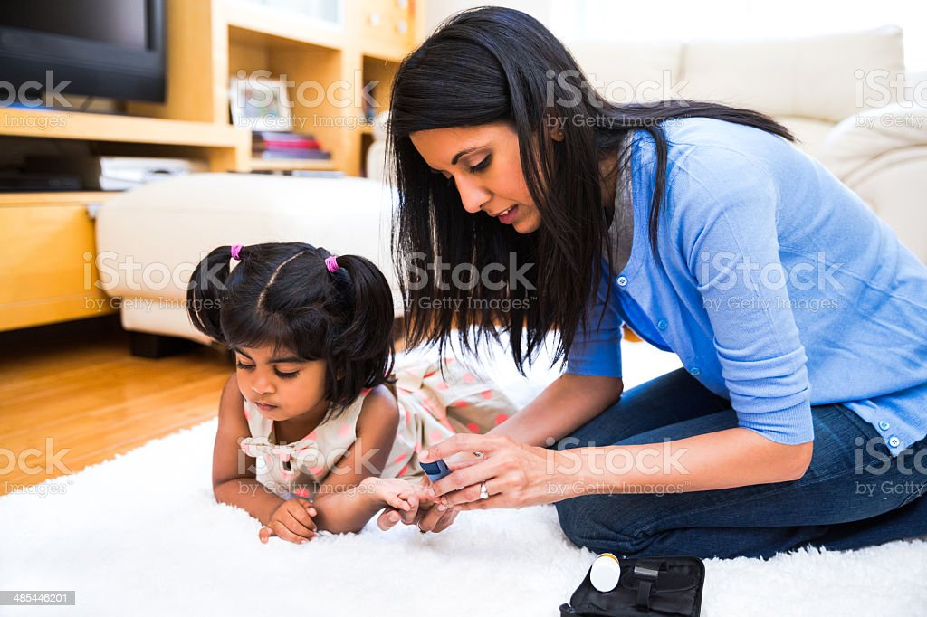 Mother is checking her daughters' diabetes. stock photo