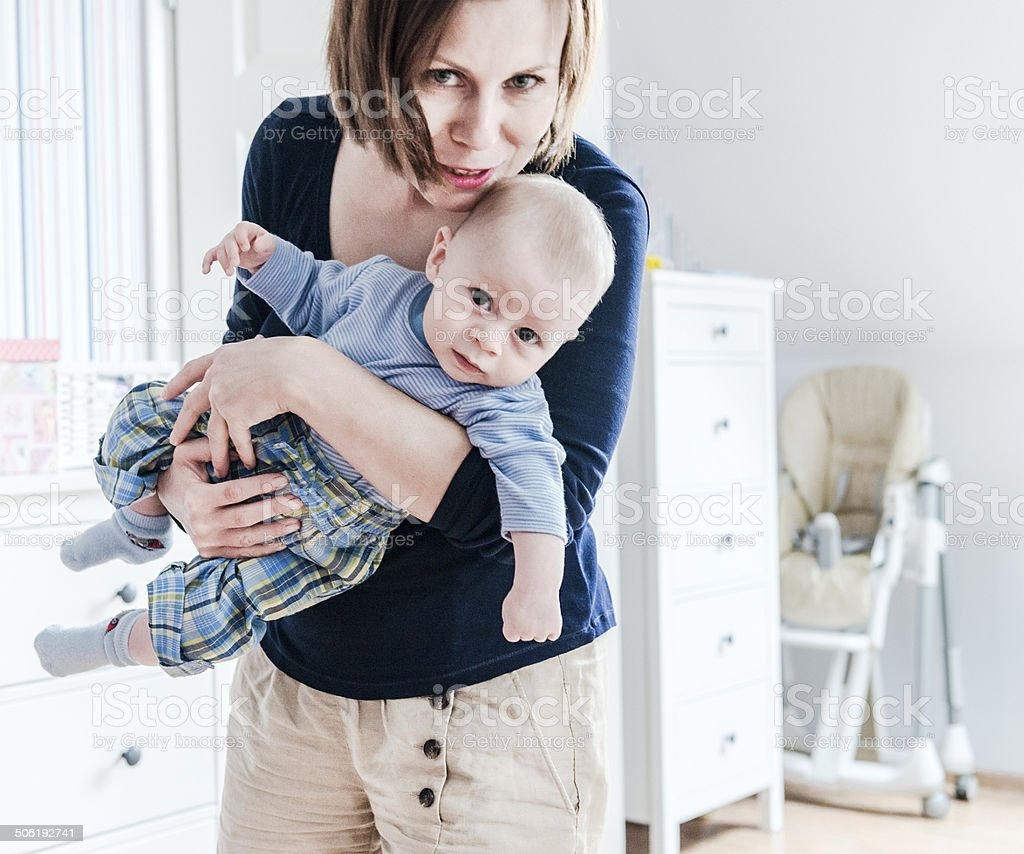 Mother is holding little baby boy on hands, baby's room stock photo