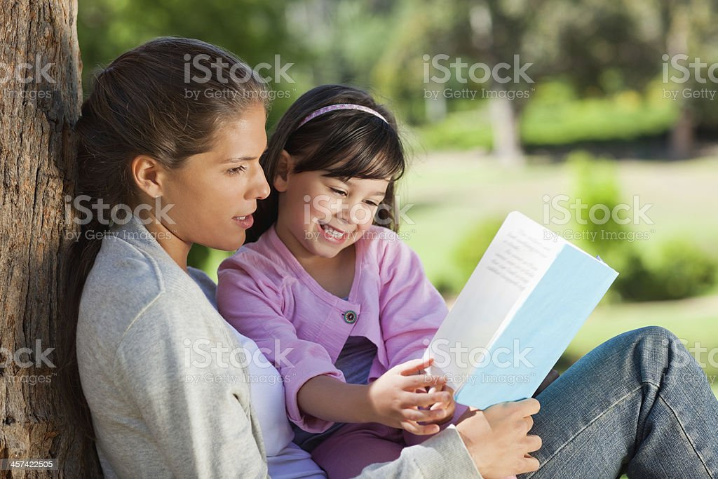 Mother is reading a book to her smiling daughter royalty-free stock photo