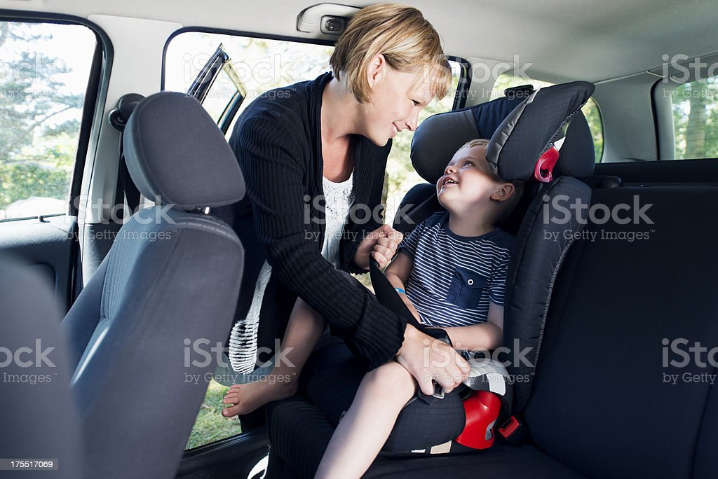 Mother is securing child in a car with seat belt stock photo