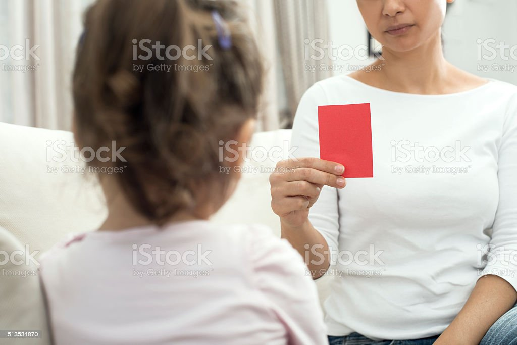 Mother is Showing Red Card to Child stock photo