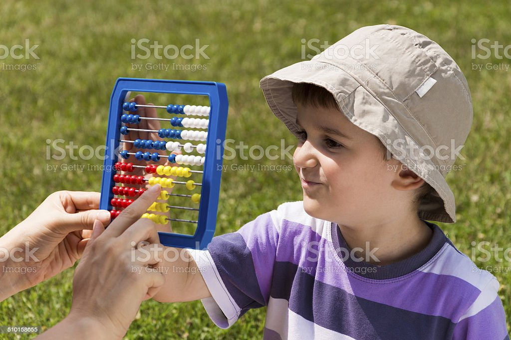 Mother is teaching her joung son to calculate stock photo