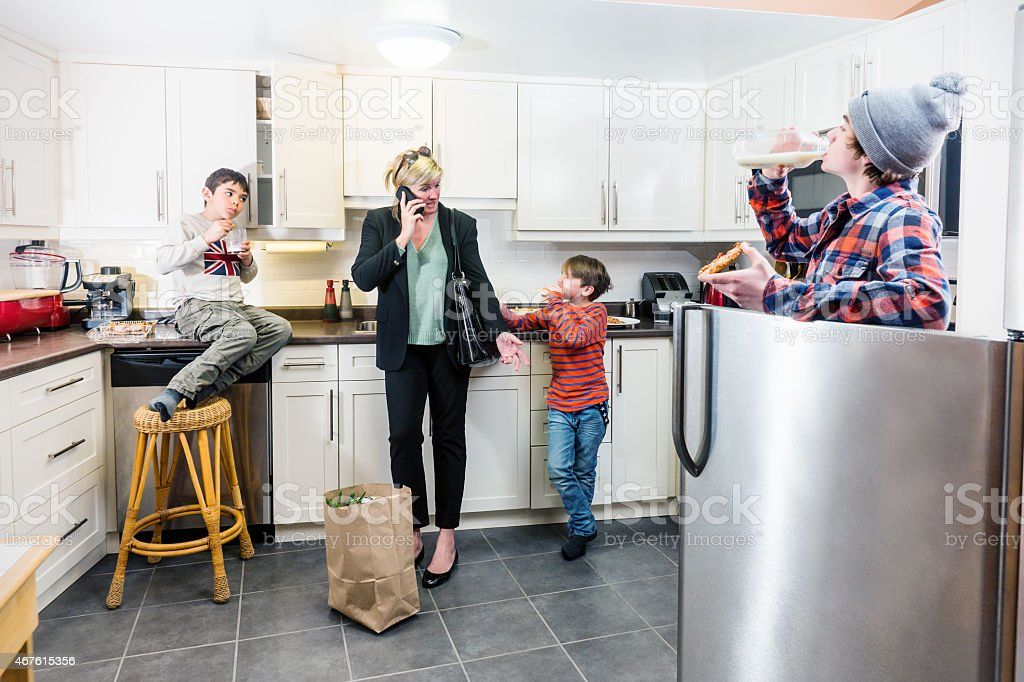 Mother just arrived home from work and already multi-tasking. stock photo