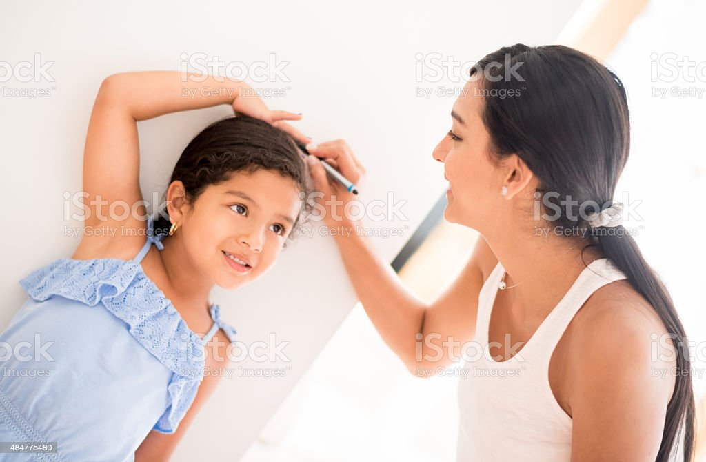 Mother keeping record of her daughter's height stock photo