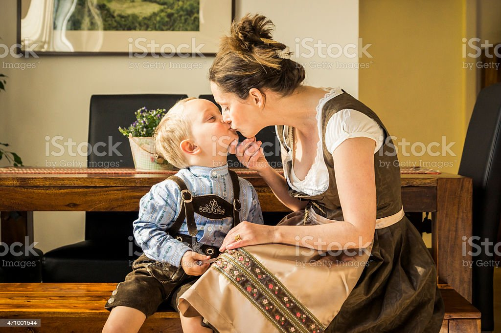 Mother Kissing Child at Home in Traditional Clothing stock photo