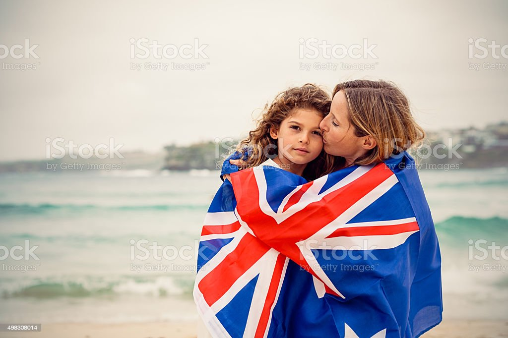 Mother kissing daughter and they are covered by Australian flag stock photo
