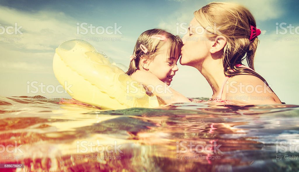 Mother kissing daughter in sea stock photo