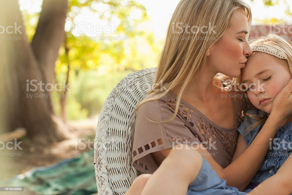 Mother kissing daughter outdoors stock photo