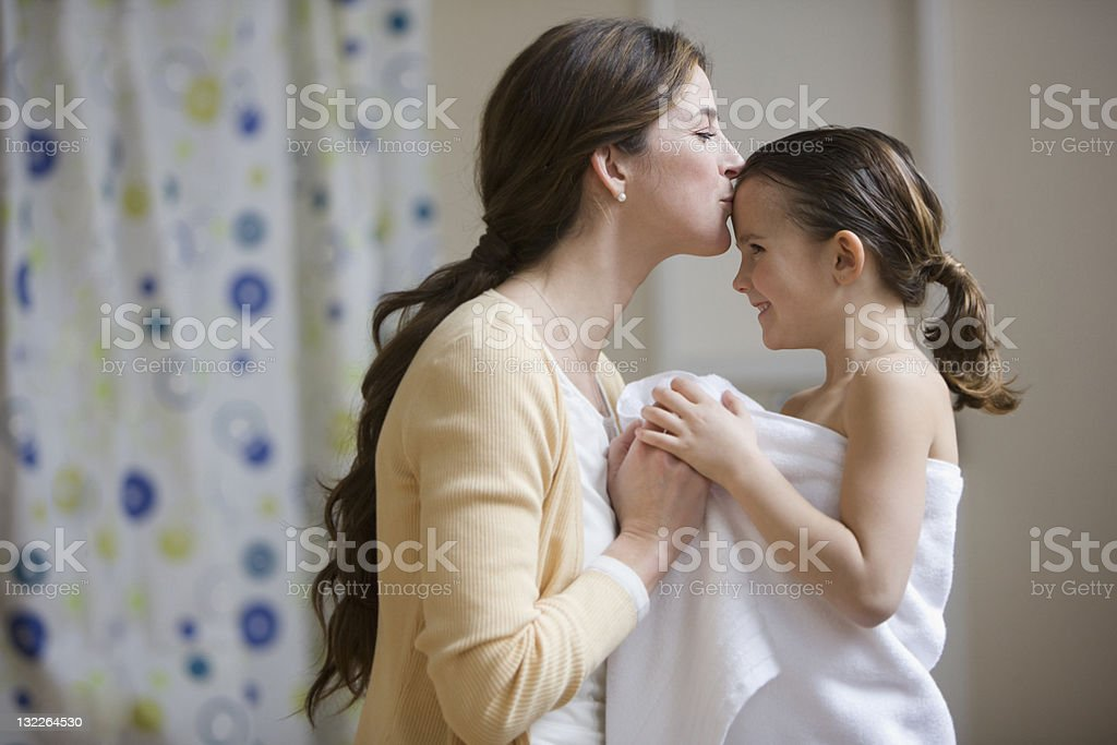Mother kissing daughter's forehead after bath stock photo