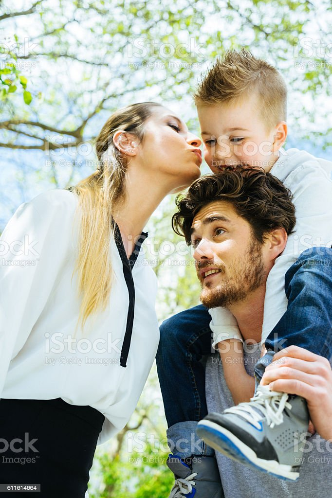 Mother Kissing Goodbye Husband And Son Before Going To Work stock photo